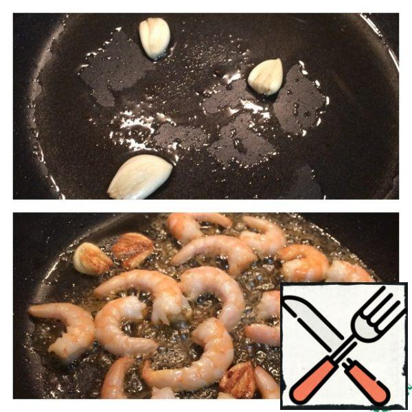 In the same pan, fry the crushed garlic cloves first, then the peeled shrimp, removing the garlic, literally 1 minute.