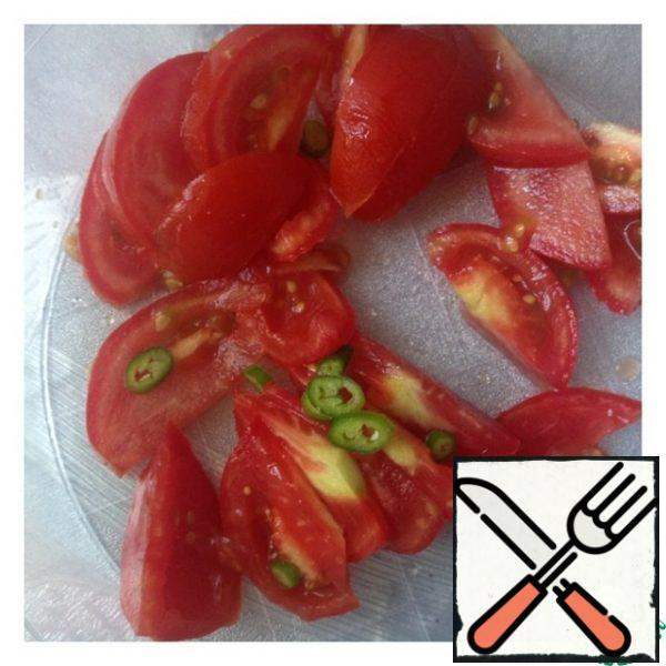 Tomatoes cut into half slices. Do not peel the hot pepper from the seeds and cut it into small circles.