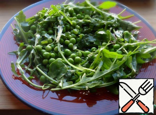 Mix the arugula and peas with the dressing and place on a plate.