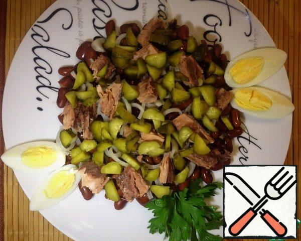 On a platter, put the beans, then the onion, half a can of canned tuna. It is suitable both in oil and in its own juice. Top with cucumbers.