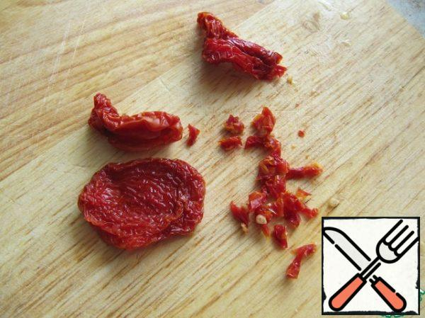 Cut sun-dried tomatoes into small pieces.