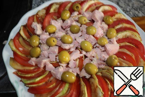 Put the olives and tuna on top of the salad in small pieces.