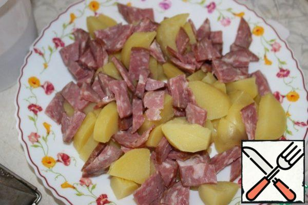 Cut the sausage into thick strips. Spread on a dish with potatoes.