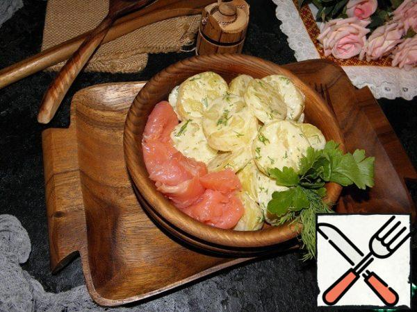 Spread the potato salad on the dish and add the fish slices.