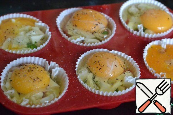 Carefully beat the egg into the mold. And try to first pour in the protein, and already pour the yolk up. Season with salt and pepper. Bake in a preheated oven at 180 g for 25 minutes.