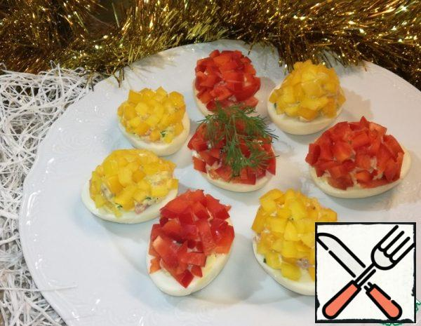 Red and yellow pepper cut into small cubes and sprinkle on top of the eggs, slightly pressing.