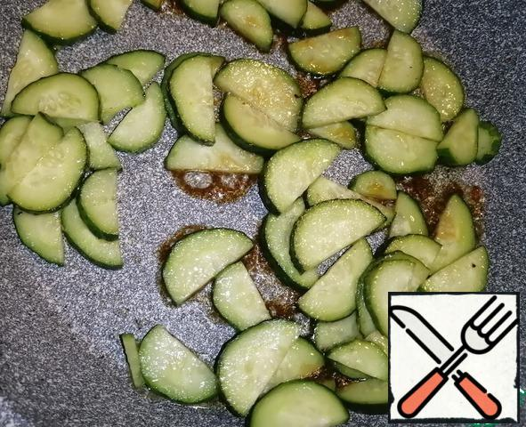 Add 0.5 tbsp of vegetable oil to the pan where the chicken fillet was fried and pour out the cucumbers. Fry for 3-4 minutes. Add soy sauce and salt to taste. Fry for another 3-4 minutes over medium heat, stirring occasionally. Pour the finished cucumbers into a bowl with the fillet.