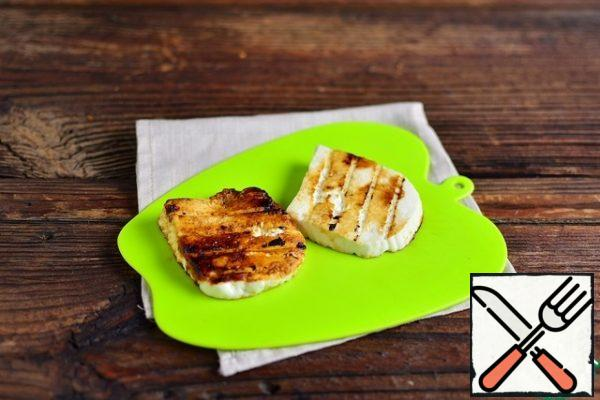 Fry two slices of cheese on the coals inside the grill, turning once until toasted, as it cools, remove from the grill.