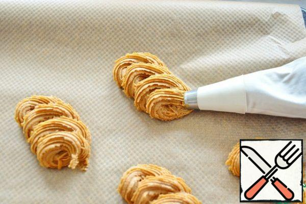 Fold the dough into a pastry bag. Put the cookies in any shape. It is better to put on parchment to make it easier to remove.From experience, I will say that the dough is quite difficult to put out of the pastry bag. You can just put it on a baking sheet with two teaspoons.