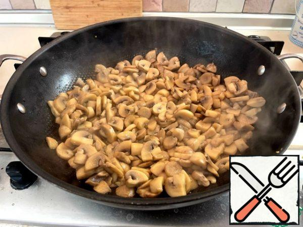 Mushrooms cut into plates 3-4 mm thick and lightly fry in a frying pan (I have a wok) in vegetable oil. I had 1 kg of mushrooms here, but after roasting, I selected half as a preparation for the future.