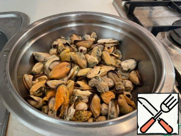 Wash the mussels thoroughly in cold water, then pour in cold water, mix, let stand for about 10-15 minutes and select the mussels with your hands in another bowl. This is necessary so that the grains of sand and shell particles remain on the bottom.
