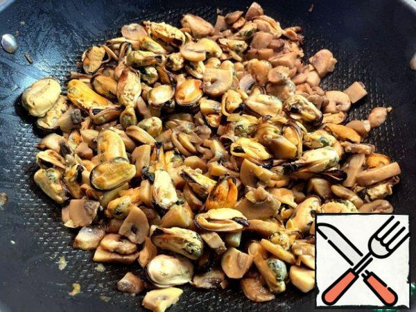 Add the mussels to the mushrooms and continue cooking over medium heat. Then add the fried onions to them.