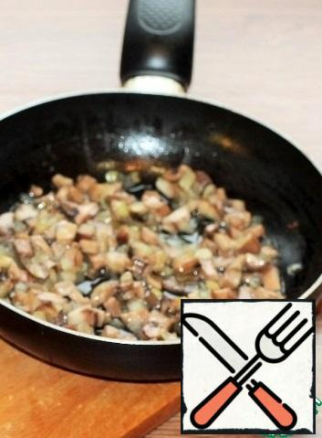 In preheated vegetable oil (3 tablespoons), fry the onion until transparent. Add the mushrooms and fry until half cooked.