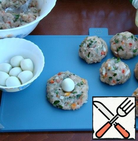 Prepare the filling for samsa. To do this, form small koloboks from minced meat, placing quail eggs inside.