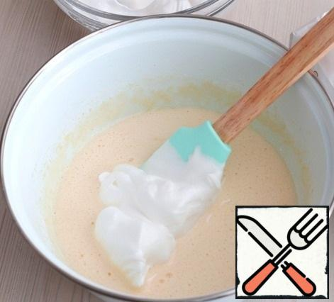 Next, to the whipped almond-egg mass, add gradually portions of whipped whites in a strong foam. Gently knead the dough from the bottom up. You should get a lush, with a light cream tint, sponge dough.