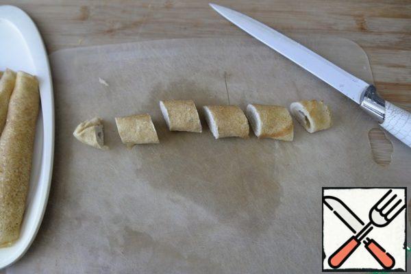Frozen pancake rolls are taken out of the freezer, cut off the edges with a sharp knife. Cut diagonally into even 4 parts.