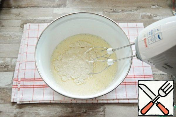 Gradually, at low speed of the mixer, add the sifted flour with baking powder.