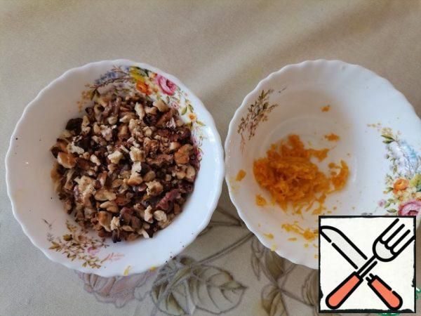Walnuts are fried and not very finely chopped. Remove the zest from the orange.