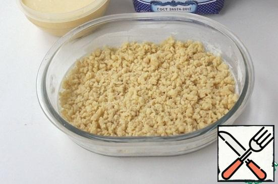 In the form of, I have somewhere size of 20*18, put half of the flour crumbs. If you have prepared the dough, then divide it into two halves and grate on a coarse grater, put 1/2 of the crumbs in the form. Level it out.