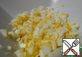 Hard-boiled eggs. Peel the boiled eggs from the shell and also cut into cubes.