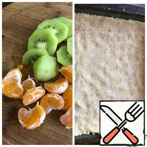 Use your hands to press the crumb directly into the mold, forming small sides. Peel the kiwi and cut it into thin slices. Peel and peel the tangerine.