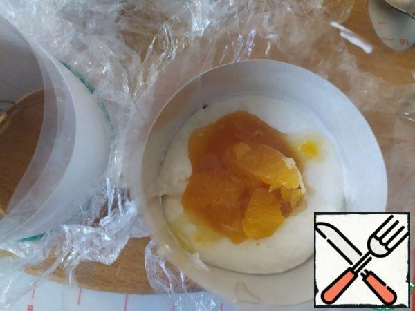 Mango puree is mixed with tangerines and spread on a layer of cheesecake.
