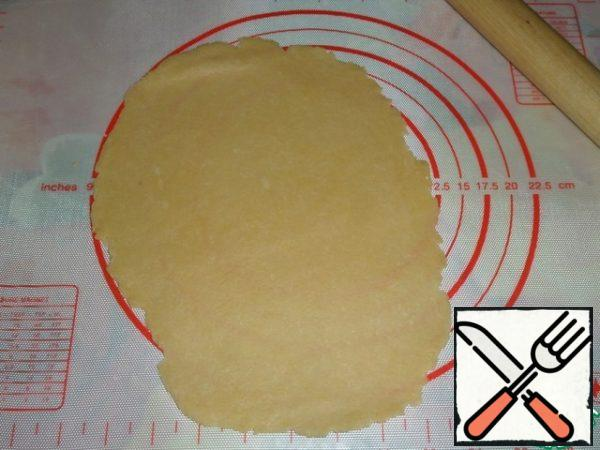 Roll out the dough in the form of a flat cake.