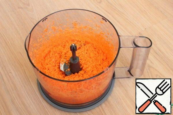 Carrots are crushed in a blender.
