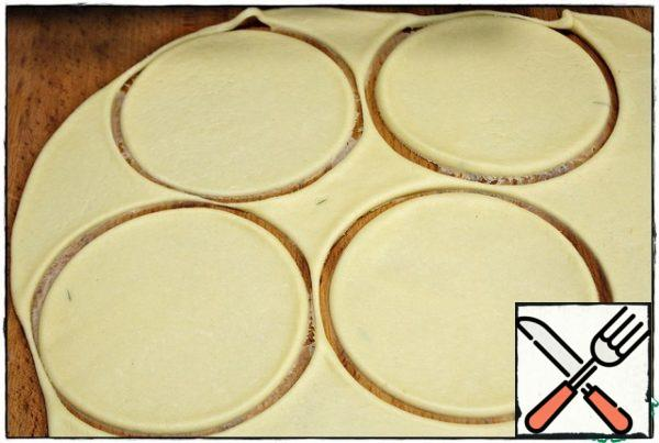 We take some saucer with a diameter of 12-13 mm and squeeze out the blanks. the rest of the dough is removed and we will roll out with the next batch of pies. from the total amount of dough i get 16 such blanks, so count the weight of the filling on about the same number of pies.