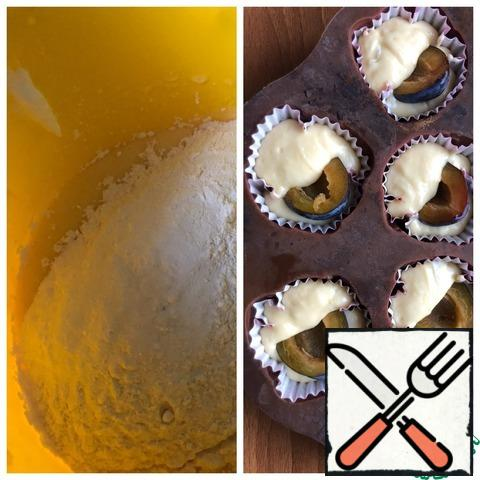Add baking powder and flour. Beat for half a minute. In paper cupcake molds, place the dough filling the form half. Peel the feijoa, divide the plum into 2 halves, and remove the stone. In the center of each cupcake, put half a plum (6 cupcakes), in the remaining 6 cupcakes, drown the feijoa.