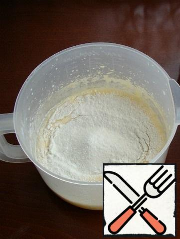 Then pour in the sifted flour and mix with a spatula or mixer at low speed.