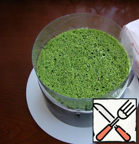 Now let's start assembling our cake. place one spinach cake on a platter. On it, apply a uniform layer of half of the cream cheese. Set the frozen vertical roll on the cream. On the roll, apply the second half of the cream and cover everything with a second spinach cake.