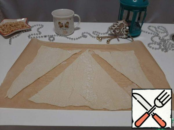 Divide it into two parts. Cut out triangles from one part of the dough layer.