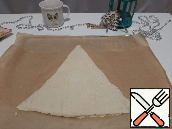 From the second part of the dough, cut out another triangle and spread it on top of the chocolate and peanuts.