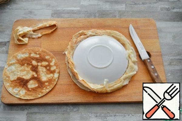 To make the edges of the cake even, cut the pancakes using a plate with a diameter of 18 cm as a template.