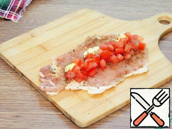 Sprinkle the meat plate with seasoning, salt, pepper and spread the tomato slices. Add the butter. Close the filling with a plate of meat and fix it with wooden toothpicks.