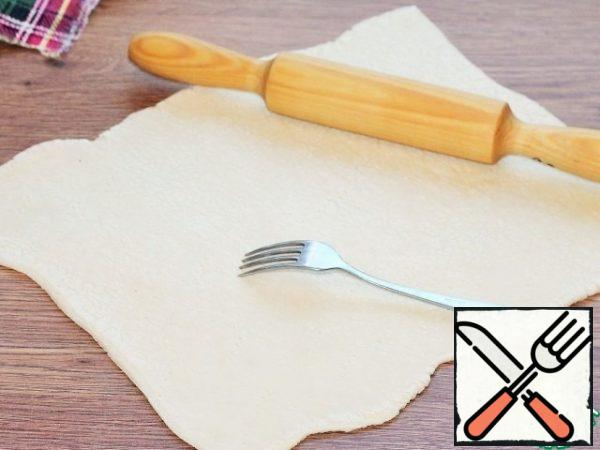 A plate of puff pastry is placed on a table top dusted with flour and rolled out 1.5 times. Pierce the dough with a fork.