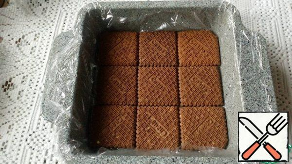 Form the size of 19 × 19 cm cover with film. Place the cookies with a flat surface facing down.