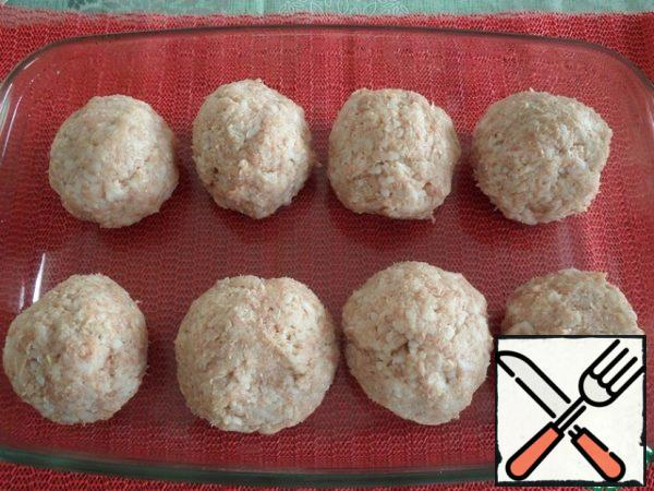 The baking dish is greased with vegetable oil (1 tbsp. l.). From the prepared chicken and rice minced meat, we make balls. We put them in the form. I got 8 pcs.