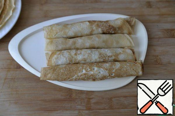Roll the pancakes into rolls. Store in the refrigerator until serving. Before serving, I advise you to send it to the freezer for 30 minutes, so that it is easier to cut.