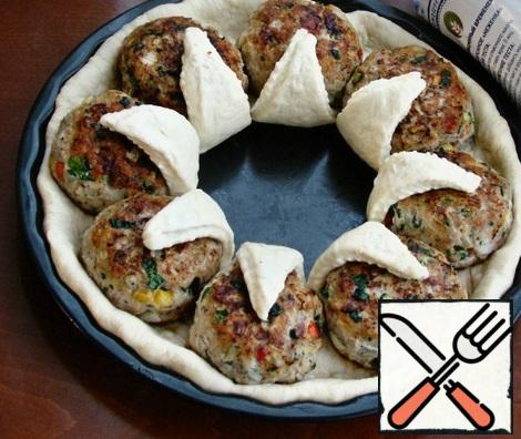 Arrange the cutlets in a circle and cover with the dough petals. In the middle, put a circle of dough, rolled out of the remaining part and fill with grated mozzarella cheese on a large grater. Just fill the space between the cutlets with cheese.