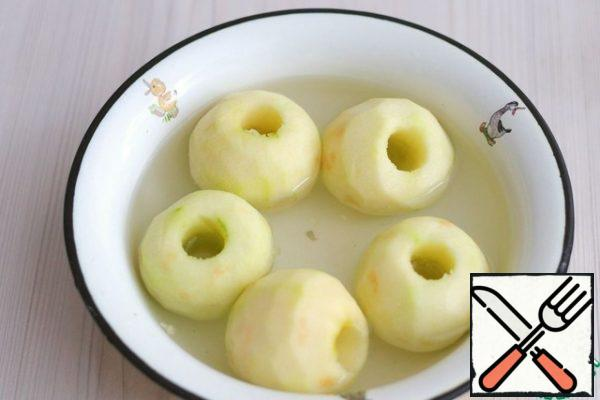 While the dough is cooling, let's start preparing the Apple filling. Apples (5 PCs.) peel, remove the core with a special knife to remove the core of the fruit. Place the apples in a solution of water and citric acid. In an acidic environment, the apples will retain their color and will not darken.