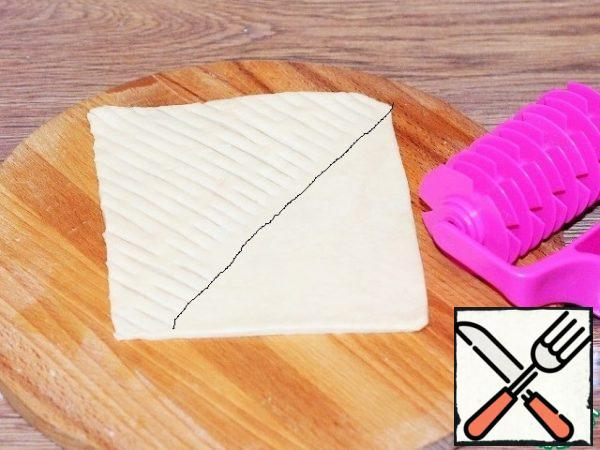 The formed pies. We take 1 part of the dough and cut the mesh into 1/2 part of the rectangle with a curly roller.
