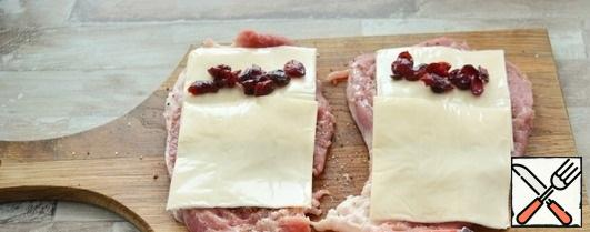 Put 2 slices of melted cheese on each piece of pork. Put 1 tsp of dried cranberries on one edge.