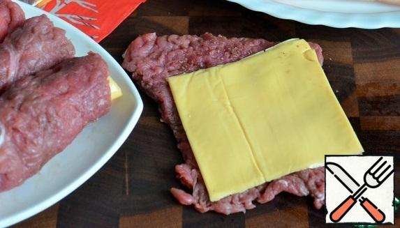 Put a slice of cheese on the layer of meat, roll it up.