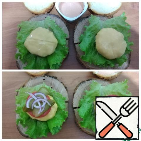 On a salad leaf-a hot cutlet with cheese. Cut the tomato into slices, cucumber and thin semi-rings of red onion. Carefully spread on the cheese. Spread the second half of the bun with sauce and cover.