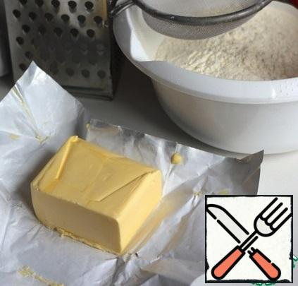 In a bowl, sift high-quality flour, mix with a whisk with a pinch of salt and vanilla. In the flour mixture, grate the frozen butter on a large grater, constantly dipping the butter in flour, rub it with your hands into small crumbs.