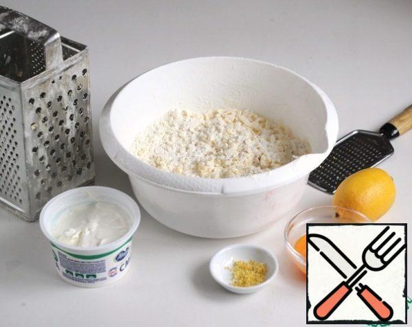 To the butter-flour mixture, add sour cream, egg yolks, lemon zest, knead the dough.