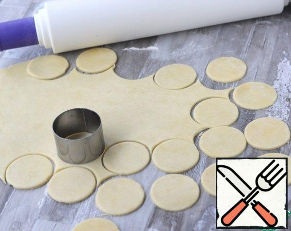 Take the dough out of the refrigerator, cut off half, put the second part back in the refrigerator. Roll out the dough into a layer 3 mm thick, cut out circles with a diameter of 6 cm.