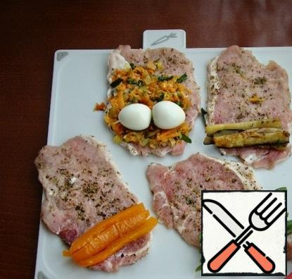 Spread the filling on meat slices and roll into rolls. Roll quail eggs together with fried carrots and onions.
